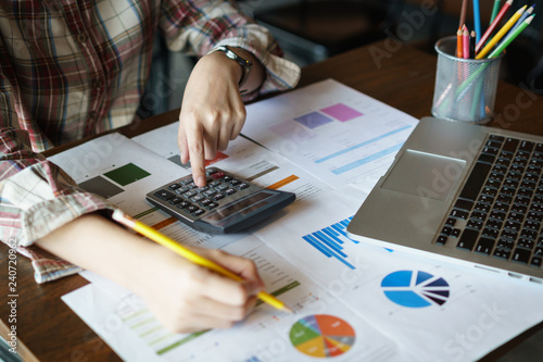 Business woman holding a pencil to analyze the marketing plan with calculator on wood desk in office. Accounting concept.Finance concept.