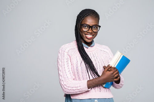 Young beauty african woman casual daily lifestyle student holding notebooks smiling isolated on grey