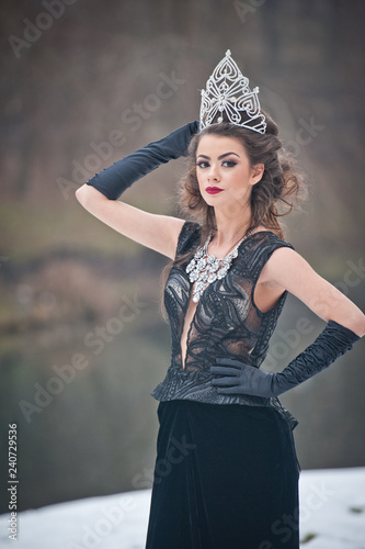 Gypsy Beautiful fairy-tale winter queen in the forest with sparkling tiara and Elegant black fur coat. Fluffy snow flakes.