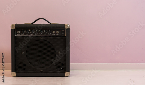 Photo portable electric guitar amplifier isolated in front of a stone wall, music equi
