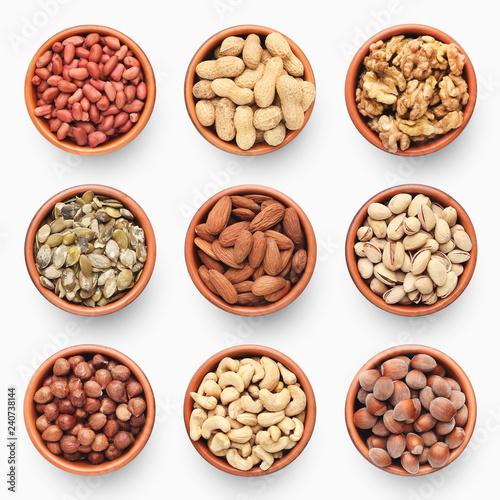 Valokuvatapetti Set of various nuts in ceramic bowls isolated on white