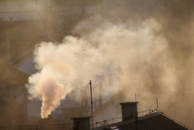 Smoking Chimneys At Roofs Of Houses Emits Smoke, Smog At Sunrise, Pollutants Enter Atmosphere. Environmental Disaster. Harmful Emissions And Exhaust Gases Into Air. Fog, Winter Day, Heating Season.