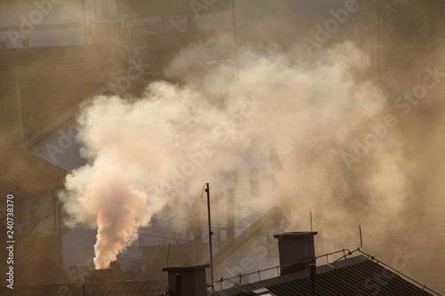 Obraz na plátně Smoking chimneys at roofs of houses emits smoke, smog at sunrise, pollutants enter atmosphere