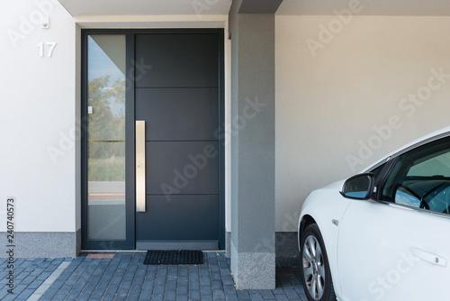 Fototapeta Modern house entrance with parking car next to it obraz