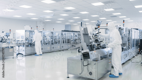 Sterile High Precision Manufacturing Laboratory where Scientists in Protective Coverall's Turn on Machninery, Use Computers and Microscopes, doing Pharmaceutics and Semiconductor Research.