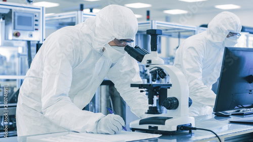Obraz In Laboratory Scientists in Protective Clothes Doing Research, Using Microscope and Entering Data into Personal Computer. Modern Manufactory Producing Semiconductors and Pharmaceutical Items. - fototapety do salonu