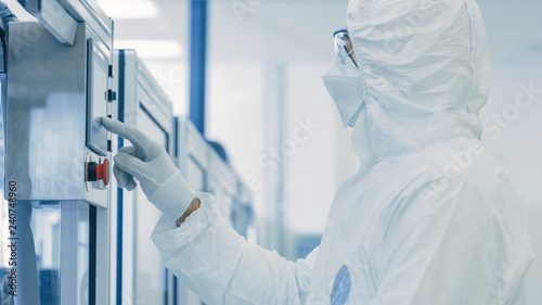 Foto In Manufacturing Facility Scientist Wearing Sterile Protective Coverall and Programs Modern Industrial 3D Printer, High Precision Manufacture of Semiconductors under Process and Presses Start Button