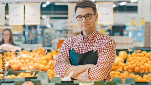 Photo At the Supermarket: Portrait Of the Handsome Stock Clerk Wearing Apron, Arranging Organic Fruits and Vegetables, He Smiles and Crosses Arms
