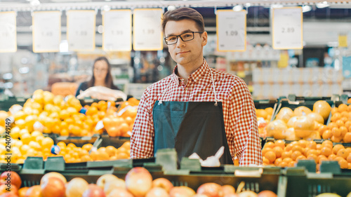 Photographie At the Supermarket: Portrait Of the Handsome Stock Clerk Wearing Apron, Arranging Organic Fruits and Vegetables, He Smiles into Camera