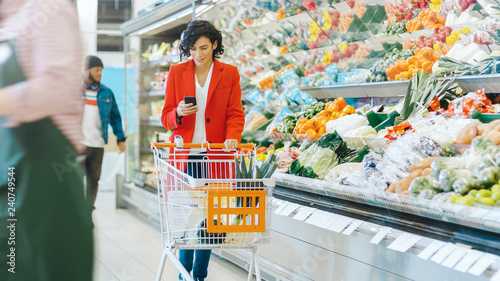 At the Supermarket: Beautiful Young Woman with Shopping Cart Uses Smartphone and Walks Through Fresh Produce Section of the Store.