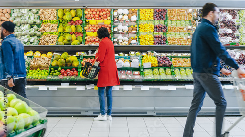 Cuadros en Lienzo At the Supermarket: Woman Chooses Organic Fruits in the Fresh Produce Section of the Store