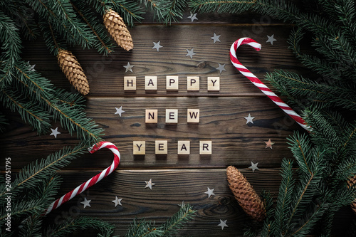 Fotografie, Obraz  Happy new year phrase on woodden rustic table surounded with fur tree branches, cones, stars and candy canes
