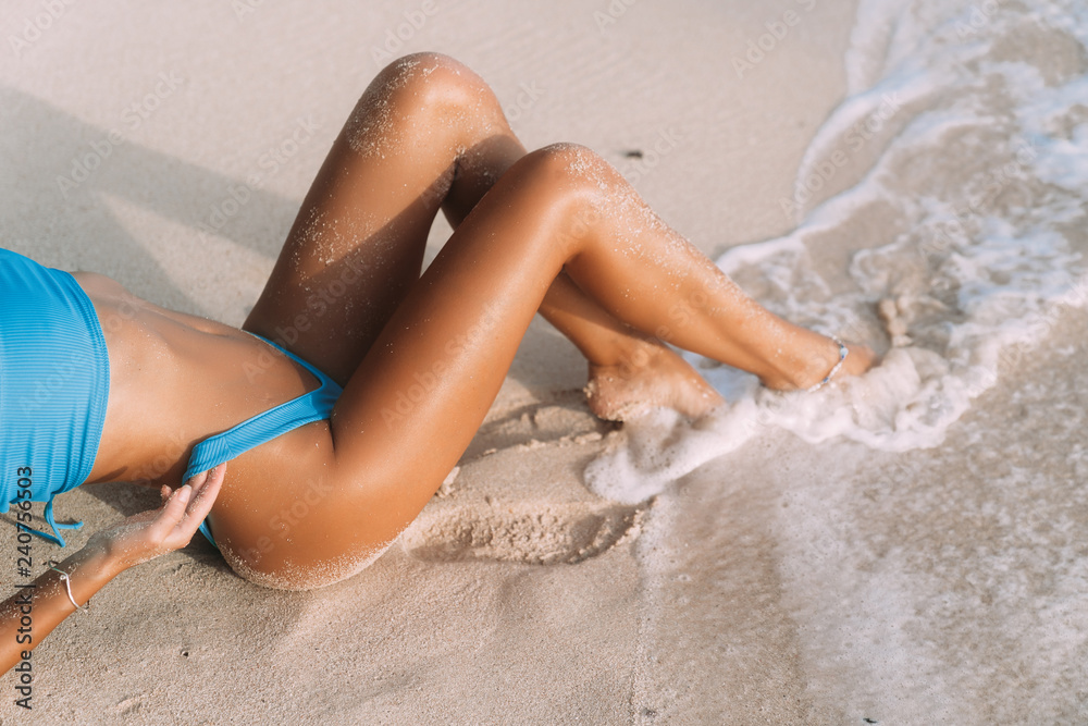 Fototapety, obrazy: Close-up tanned parts of female body on the beach with white sand. Sexy model in a blue bikini. Woman in a swimsuit on summer vacation.