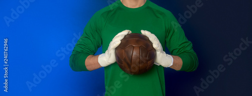 Foto soccer goalkeeper holding old soccer ball in hand with gloves on blue background