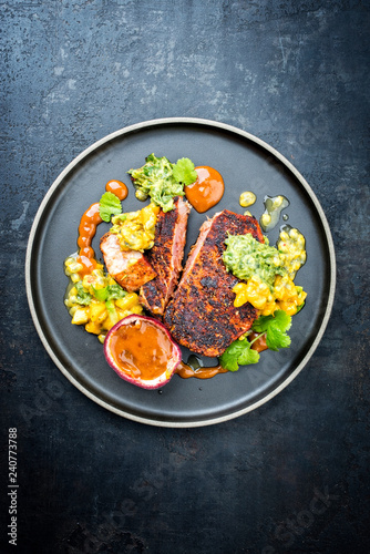 Traditional exotically blackened Cajun style tuna fish fillet with mango avocado salad, chimichurri dip and spicy BBQ sauce as top view on a modern design plate