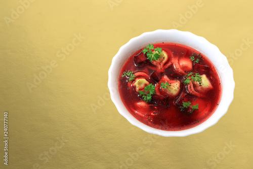 Fototapeta Barszcz czerwony z buraczków z uszkami i pietruszką na złotym tle. obraz