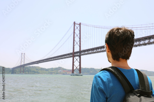 Back view of young backpacker man looking at bridge. Traveler or tourist with backpack on the waterfront in Lisbon Portugal next to the 25th of April Bridge.