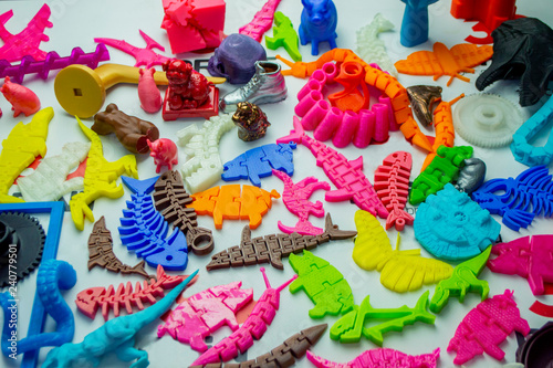 Fotografía Many bright multi-colored objects printed on 3d printer lie on flat surface close-up