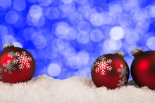 Close Up On Three Red Bauble, Blue Bokeh Lights In Background. Christmas Greeting Card Concept.