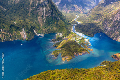 Poster Oceanië New Zealand. Milford Sound (Piopiotahi) from above - the head of the fiord with wharf and Milford Sound Airport. There is Cleddau River in the background