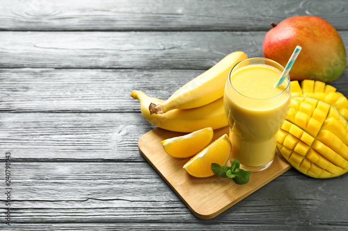 Tasty tropical drink with mango and fresh fruits on wooden table. Space for text