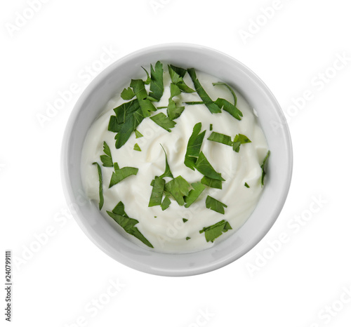 Bowl with sour cream and herbs on white background, top view