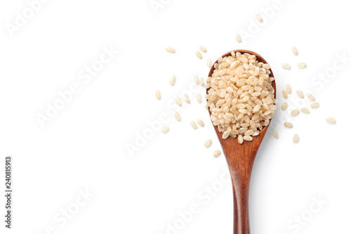 Fotografía Brown rice in a wooden spoon isolated on white background