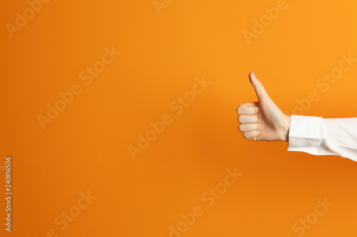 Fotografie, Obraz  Young woman showing thumb sign on color background