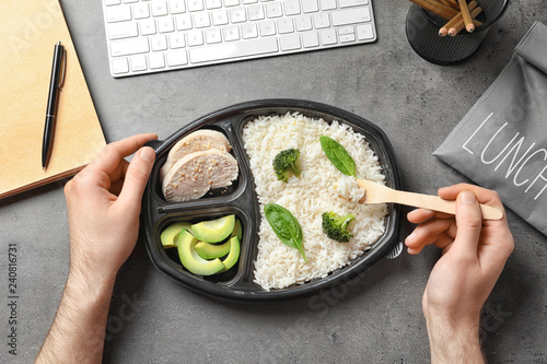 Man eating natural protein food from container at office table, top view