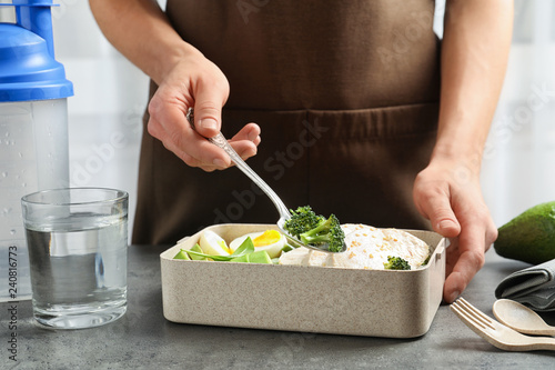 Woman putting natural protein food into container on gray table, closeup