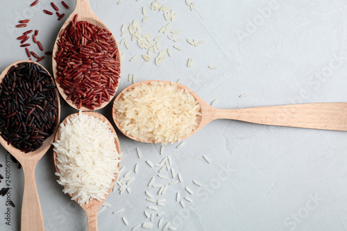 Flat lay composition with brown and other types of rice in wooden spoons on grey background