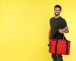 canvas print picture - Young courier with thermo bag on color background, space for text. Food delivery service