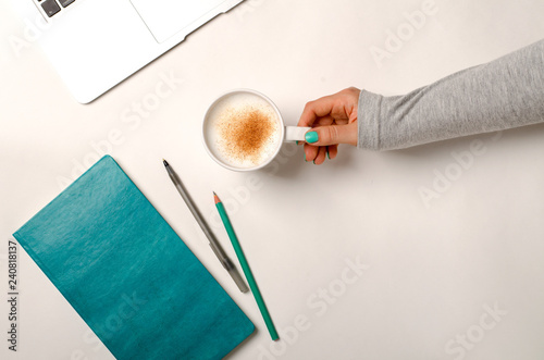 Work space with laptop, turquoise notebook and female hands holding cup of coffee. Flat lay, top view