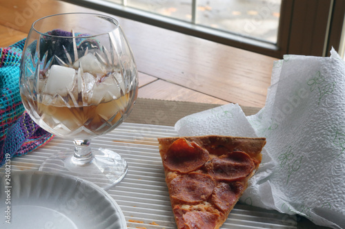 Fotografie, Obraz  Leftover slice of pepperoni pizza with cola soft drink on ice in a glass