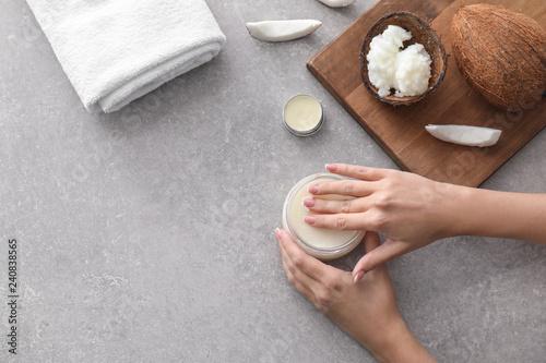 Fototapeta Woman applying coconut oil onto skin on grey background obraz