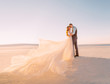 canvas print picture - Unusual wedding in the desert. A girl in a white dress ivory shade. Very long plume fluttering in the wind. A loving couple is embracing tenderly against the background of white sand and blue sky