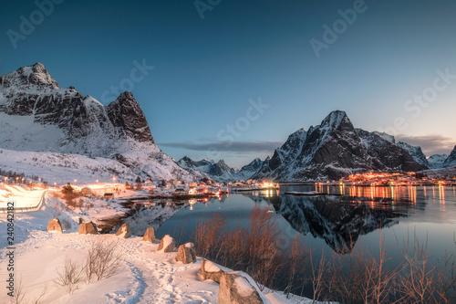 Foto auf Gartenposter Nordlicht Fishing village illuminated in mountain valley reflection on winter at dawn