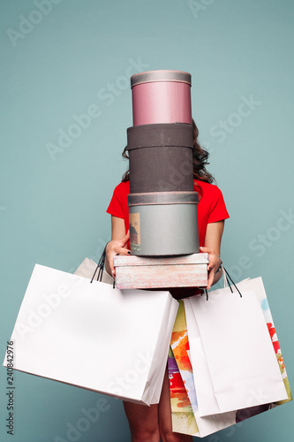 Fotografía  Studio portrait of incognito brunette woman in red dress holding at hands many bags, boxes and presents after shopping