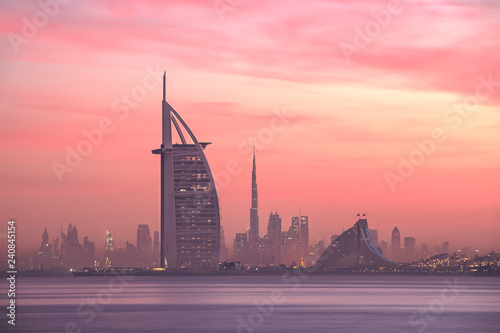 Fotografie, Obraz  Stunning view of Dubai skyline from Jumeirah beach to Downtown lighted with warm pastel sunrise colors