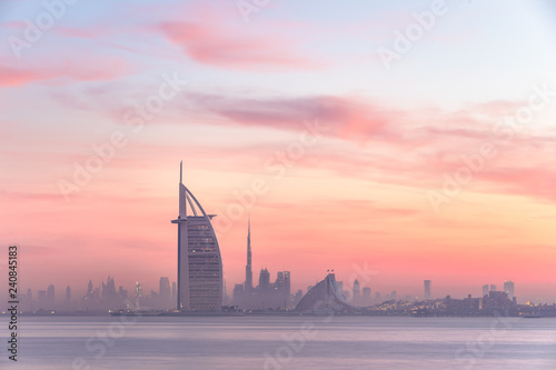 Stunning view of Dubai skyline from Jumeirah beach to Downtown lighted with warm pastel sunrise colors фототапет