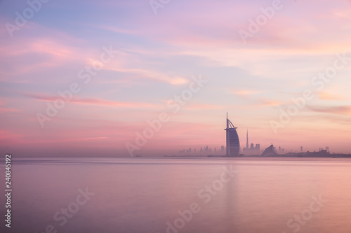 Stunning view of Dubai skyline from Jumeirah beach to Downtown lighted with warm pastel sunrise colors Wallpaper Mural