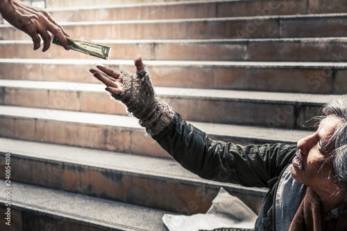 mercy hand give money to hand of poor homeless beggar selective focused Wallpaper Mural