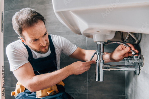 Obraz serious male plumber in working overall fixing sink in bathroom - fototapety do salonu