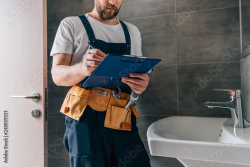 partial view of male plumber with toolbelt writing in clipboard near broken sink Wallpaper Mural