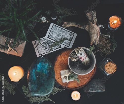 Photo Dark flat lay of witchy items from nature including evergreens, burning candles,