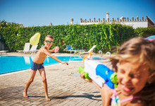 Girl And Boy Having A Water Fight With Water Gun And Water Bombs At The Poolside