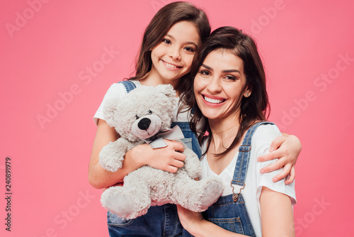 Fototapeta  smiling daughter hugging mother and holding soft toy isolated on pink