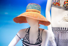 Two Mannequins In Bright And Colorful Beach Hat And Swimwear On Light Blue Background.
