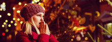 Outdoor Photo Of Young Beautiful Happy Smiling Girl Posing In Street. Festive Christmas Fair On Background. Model Wearing Stylish Winter Coat, Knitted Beanie Hat, Scarf.