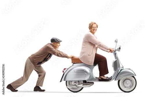 Elderly man pushing an elderly woman on a vintage motorbike